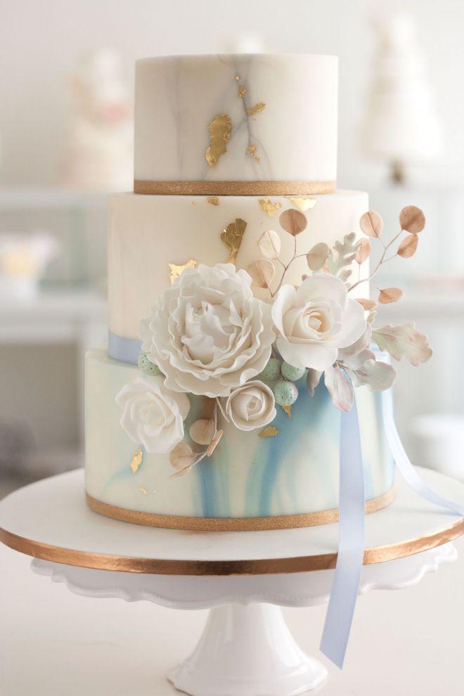 Сватбена торта на три етажа в синьо със захарни цветя и зеленина